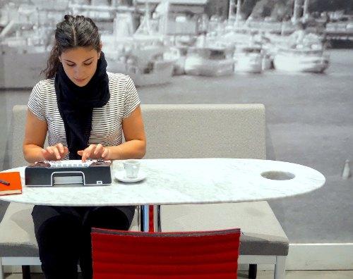 Jonge vrouw typt aan een tafeltje. Bron: Astrohaus